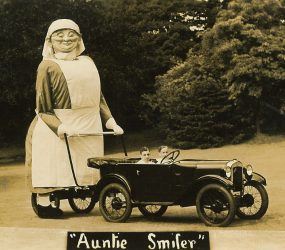 Giant model figure of smiling nurse attached to back of car to look like pushing a pram