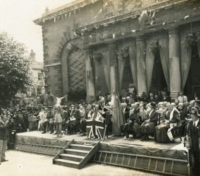 Audience and dignitaries seated on platform outside town hall