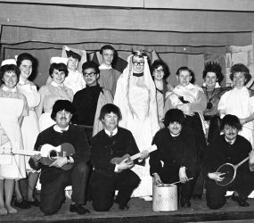 Cast in costume, some nurses uniform with four 'Earwigs', mimicking the Beatles.