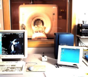 View of MRI scanner from control room, with computer screens