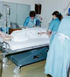 Intensive care patient in bed with staff treating