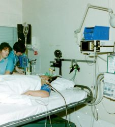 Intensive Care patient in bed with staff attending