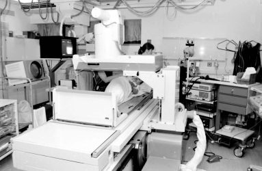 patient lies under image intensifier equipment, monitors surround, staff members attend