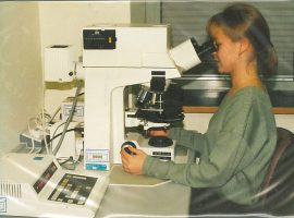 woman viewing samples through powerful multi-lens microscope
