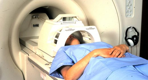 patient wearing head guard about to enter scanner