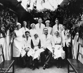 Doctors and nurses pose in corridor decorated with branches