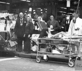 Staff dressed up, one as a patient on trolley with Mayor Councillor Biddle
