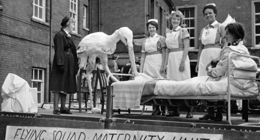Model stork with mother in bed and maternity staff on back of carnival float