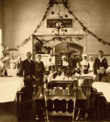 Patients sitting up in beds, garlands decorating the walls