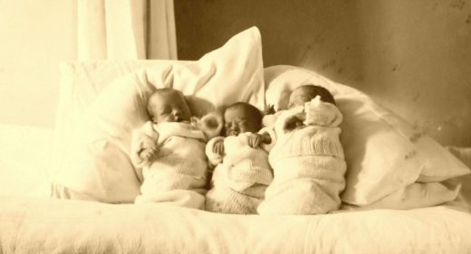 Three babies wrapped up in blankets and propped up pillows