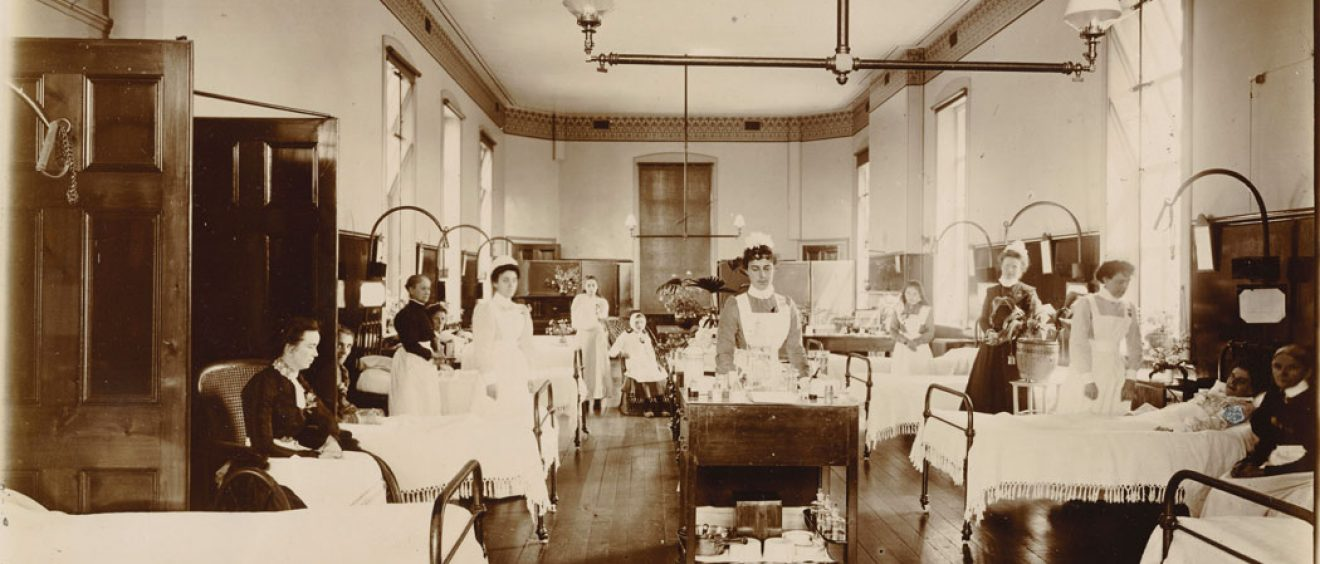 Nurse pushing drug trolley between beds on ward