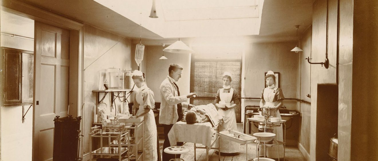 Patient on operating table with lighting, equipment nurses and doctor attending
