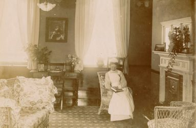 Nurse in uniform, seated reading book in sitting room