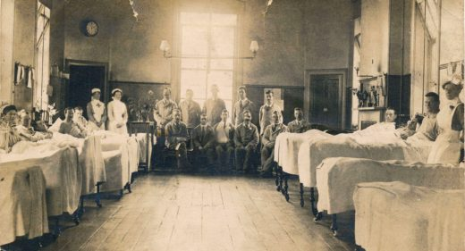 Patients in beds either side of ward and seated at the end with nurses