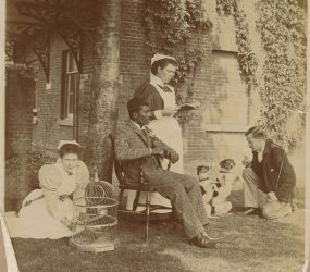 Nurse Mrs Shellcross stands centre, nurse sat on grass beside with a bird cage, man seated, another man on grass with two dogs sat on their hind legs