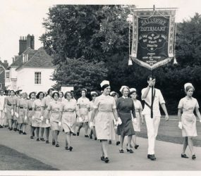 Nurses in uniform with banner carried at front