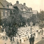 Youth marching in parade dressed in shorts, shirt and tie