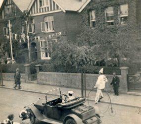 A car drives alongside a clown on a penny farthing