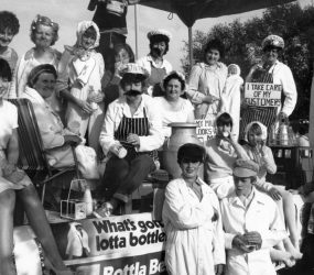 Staff dressed as milkmen carrying pints - banner on float reads 'what's gotta lotta bottle?'