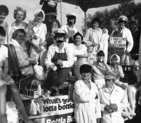 Staff dressed as milkmen carrying pints - banner on float reads 'what's gotta lotta bottle?'