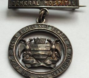 Badge with words 'the sick and needy shall not always be forgotten'
