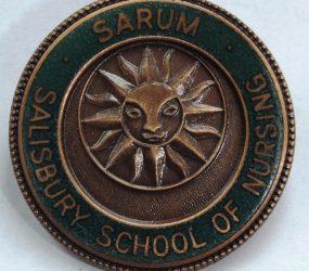 Metal badge with sun inscription inside green circle