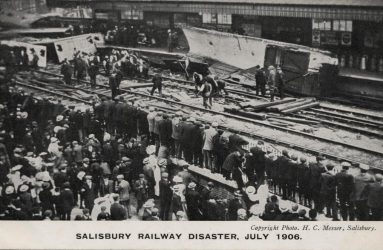 Crowds outside station look on at train wreckage July 1906