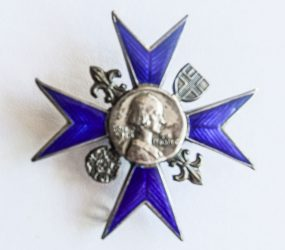 metal badge with eight point blue cross with portrait of Florence Nightingale centre
