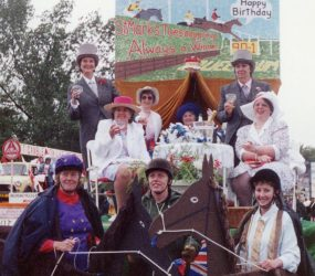 Staff on float dressed up in posh attire with others dressed as jockeys with horse costume