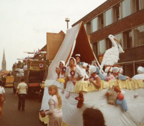 Float decorated as crib with staff dressed as babies and a giant stork inside