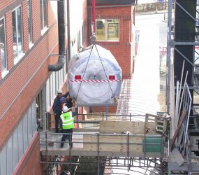MRI scanner on end of crane hook about to enter the side of hospital building