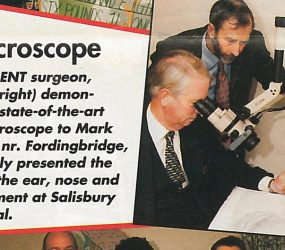 Consultant surgeon looking through microscope at patients ear