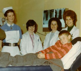 nurse and radiology staff stand by boys bed, x-rays on viewer behind bed