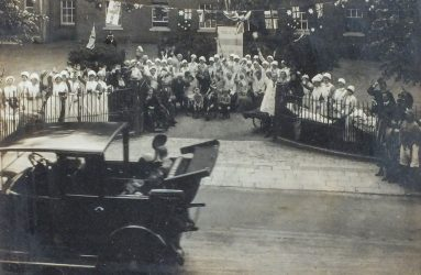 Old motor car driving past hospital staff and patients standing outside Infirmary gates waving