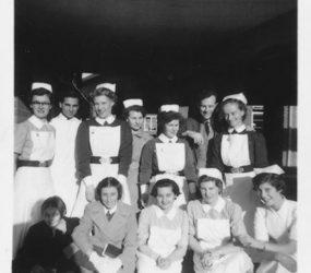 nurses pose outside central corridor buildings