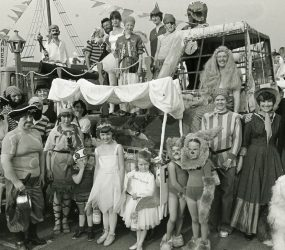 Staff and children dressed as pirates and other characters stand next to float