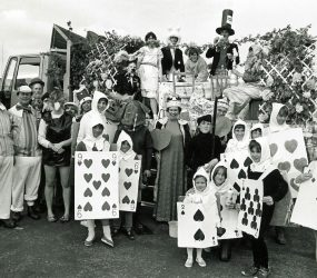 Children in playing card costumes, staff as Mad Hatter, white rabbit etc.. stand next to float