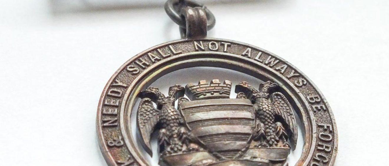 bronze metal badge with Salisbury city crest and Infirmary motto