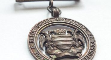 bronze metal badge with Salisbury city crest and Infirmary motto