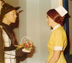 Nurse in yellow uniform with Duchess of Kent holding small flower basket