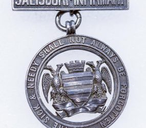 silver metal badge with Salisbury city crest and Infirmary motto