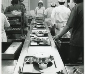 catering staff standing alongside conveyer belt loading trays with food