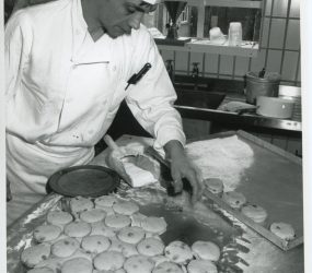 chef cutting out scones from dough and putting on tray