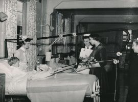 Princess with nurses talking to boy in traction on a bed in ward