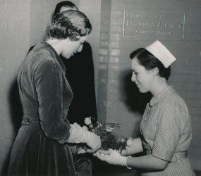 nurse handing bouquet of roses to Princess
