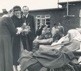 patients in wheelchairs, wrapped in blankets meet Princess Alexandra outside