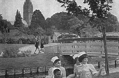 Student nurses sitting on river bank, Salisbury Cathedral in background
