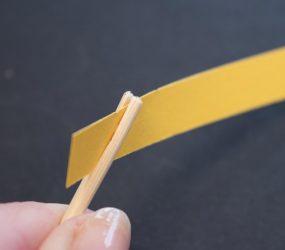 strip of paper held in slit of one end of wooden skewer