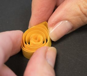 using fingers to pinch one edge of paper coil to form a point