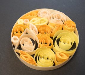 coiled strips of paper in varying shades of yellow clustered together inside a larger paper circle